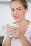 Radiant blonde woman drinking coffee