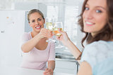 Happy women holding glasses of white wine