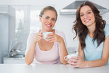 Cheerful friends having cup of coffee