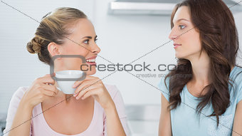 Smiling blonde looking at her friend and drinking coffee