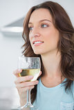 Thoughtful brunette drinking white wine