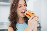 Pretty brunette eating sandwich