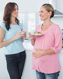 Smiling pregnant woman holding cookies and her friend