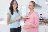Smling pregnant woman holding cookies and her friend