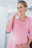 Happy expecting woman drinking milk