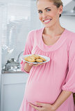 Happy expecting woman offering biscuits