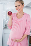 Expecting woman holding apple
