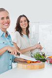 Women preparing a salad together smiling at camera