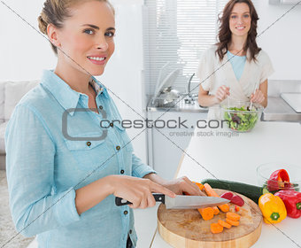 Blonde woman cutting carrots with her friend tossing salad