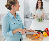 Smiling woman cutting carrots with her friend tossing salad
