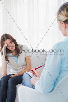 Worried woman sitting with therapist taking notes