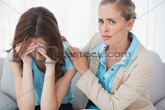 Crying woman with her worried therapist