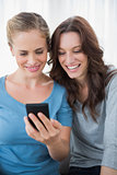 Smiling friends reading message on their phone