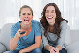 Laughing women watching television