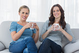 Friends having coffee while sitting on the sofa