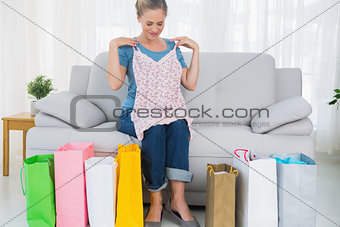 Blond woman with shopping bags trying out a top