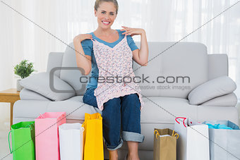 Smiling blond woman with shopping bags trying out a top