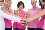 Cheerful women posing in circle holding hands wearing pink for breast cancer