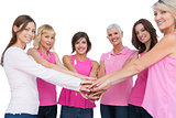 Cheerful women posing in circle holding hands looking at camera wearing pink for breast cancer