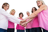 Women posing in circle holding hands looking at camera wearing pink for breast cancer