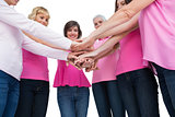 Enthusiastic women wearing pink for breast cancer posing in circle holding hands looking at camera