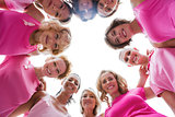 Cheerful women smiling in circle wearing pink for breast cancer