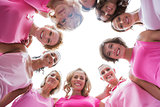 Happy women smiling in circle wearing pink for breast cancer