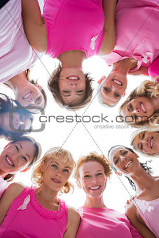 Group of women in circle wearing pink for breast cancer
