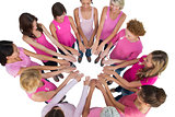 Cheerful women joined in a circle and looking at each otherwearing pink for breast cancer