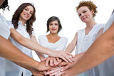 Cheerful models joining hands in a circle and looking at camera