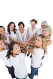 Happy female models joining hands in a circle and looking at camera