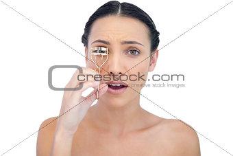 Astonished natural brunette with eyelash curler