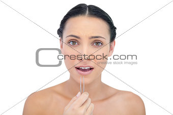 Astonished young model with tweezers