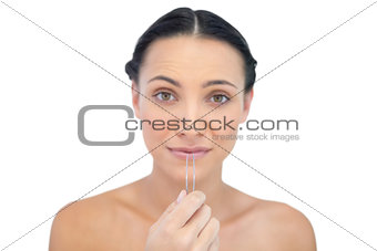 Anxious young brunette with tweezers