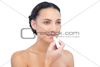 Thoughtful natural model applying chap stick