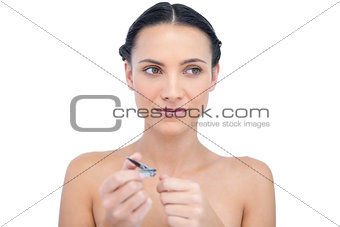 Thoughtful young model using nail clippers