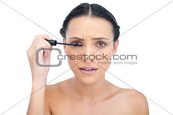 Annoyed young brunette applying mascara