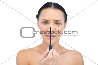 Annoyed young brunette looking at her mascara