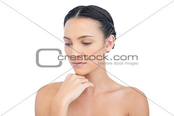 Thoughtful nude model posing hand on her chin