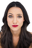 Doubtful dark haired woman with red lips