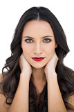 Dark haired woman with red lips touching her neck