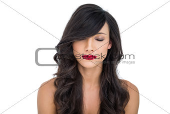 Thoughtful dark haired woman posing closing eyes