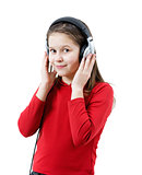 A smiling child girl listens to music through headphones