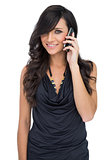 Cheerful brown haired model posing holding smartphone