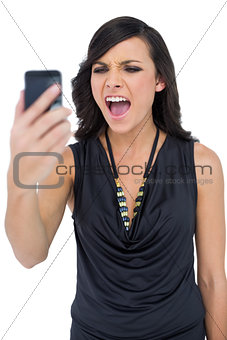Angry elegant brown haired model screaming to her phone