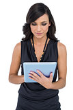 Elegant brown haired model typing on tablet