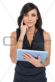 Thoughtful elegant brown haired model holding tablet