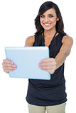 Smiling elegant dark haired model holding her tablet