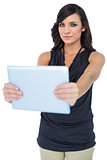 Serious elegant dark haired model holding her tablet