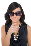 Elegant brunette wearing sunglasses pointing at camera